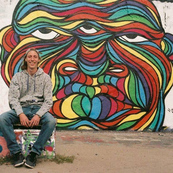 """Hans From Space mit """"Bruddha"""", Profilfoto mit Wandgestaltung / Graffiti in Regenbogen-Farben im Hintergrund, Berlin Mauerpark"""